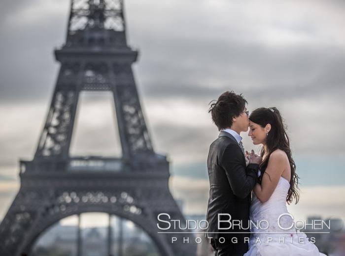 couple de mariés devant la tour Eiffel. ciel nuageux
