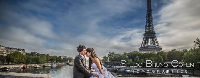 couple de mariés assis enlacés devant la Tour Eiffel ciel bleu le matin