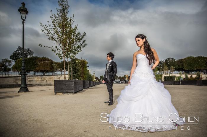 mariés sérieux qui regardent à gauche, debout à 5m de distance au Jardin des Tuileries, Paris, ciel nuageux
