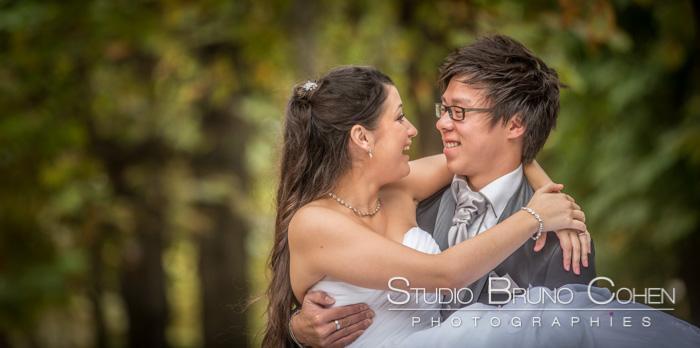 mariés qui rient en se regardant, l'homme tient la mariée dans ses bras, fond d'arbres flous en arrière-plan