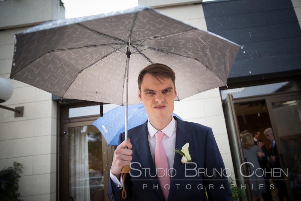 mari avec son parapluie sous la pluie a l'entree de la mairie
