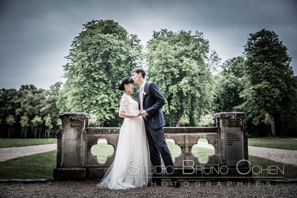 couple de marié de profil devant une balustrade du parc de l'Abbaye de Royaumont