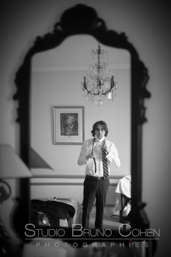 le marie se regarde dans le miroir pour enfiler sa cravatte