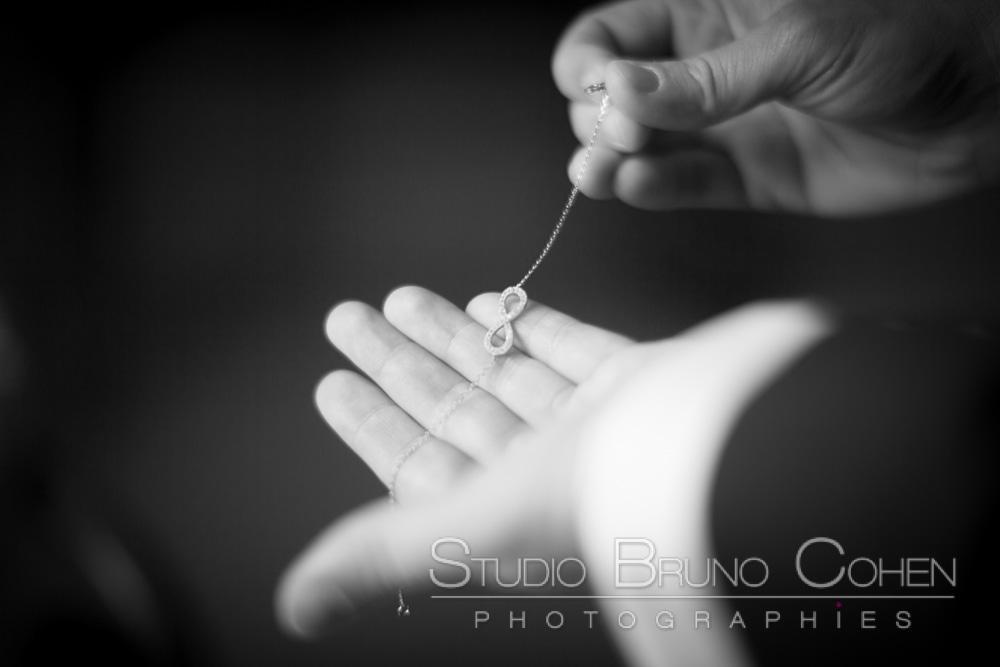 collier signe de l'infini dans les mains de la mariee