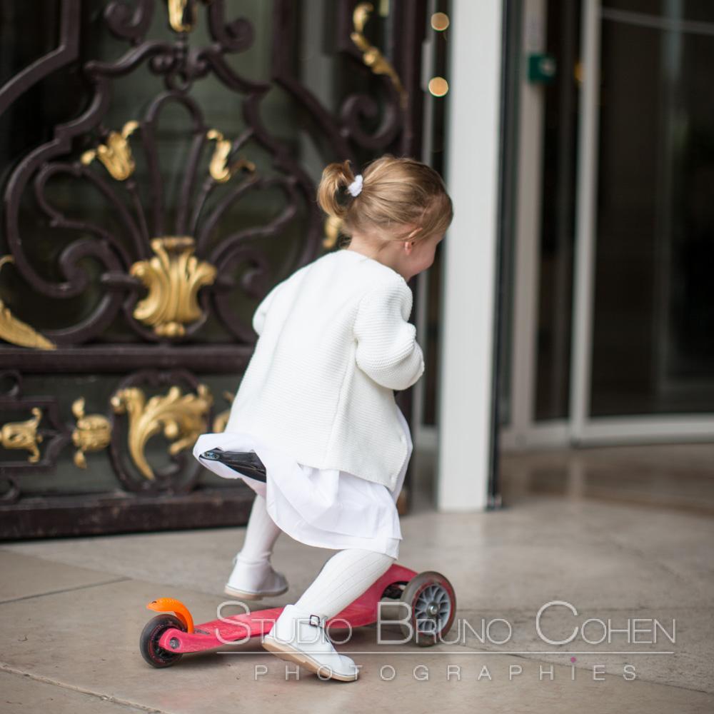 une enfant joue a la trotinette devant l'entree de la mairie