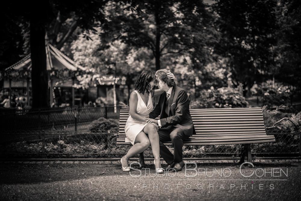 les maries assis sur un banc avec en arriere plan un manège