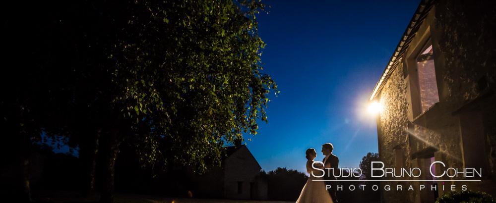 couple de mariés au crépuscule, arbre en contre jour à gauche, batisse ancienne et candélabre à droite