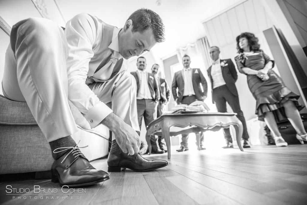 marié assis lassant ses chaussures dans la chambre d'hotel avec ses témoins en arriere plan