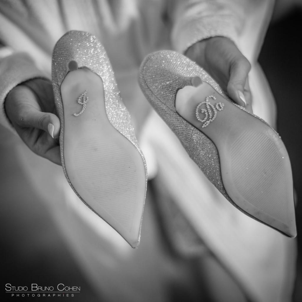 deux escarpins tenus dans les mains d'un homme montrant les semelles avec des inscriptions