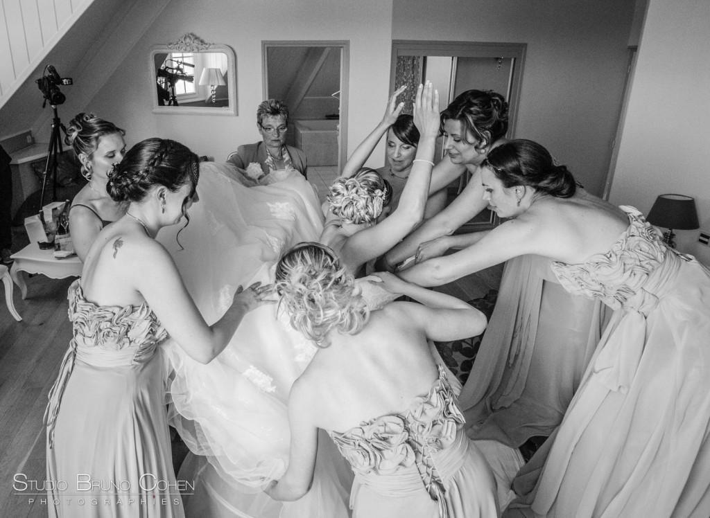 mariée enfile sa robe entourée de six femmes