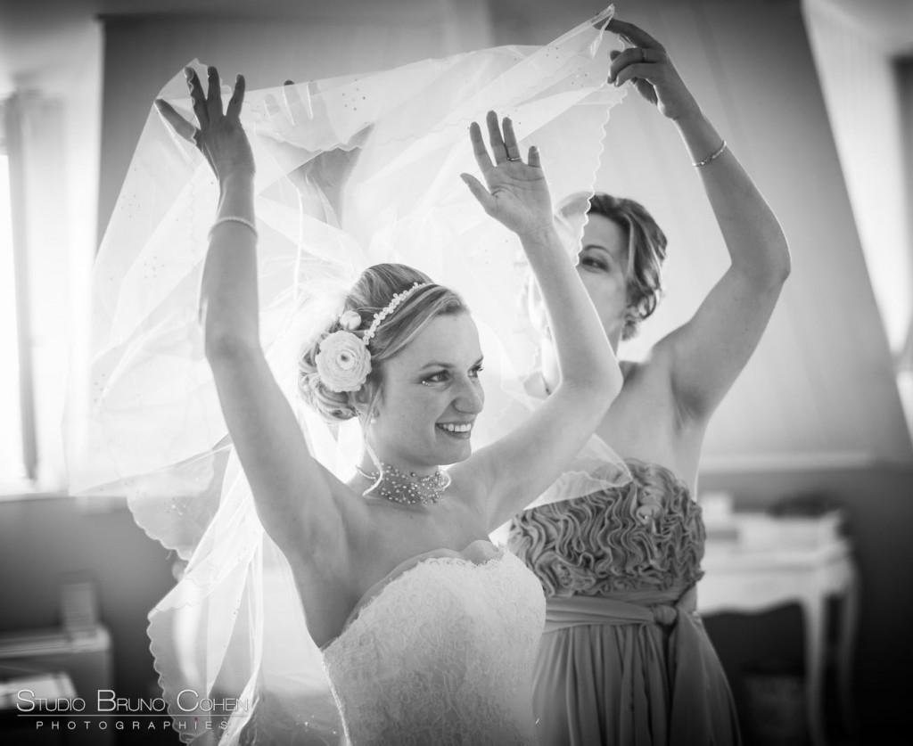mariée en noir et blanc les bras levée tient son voile