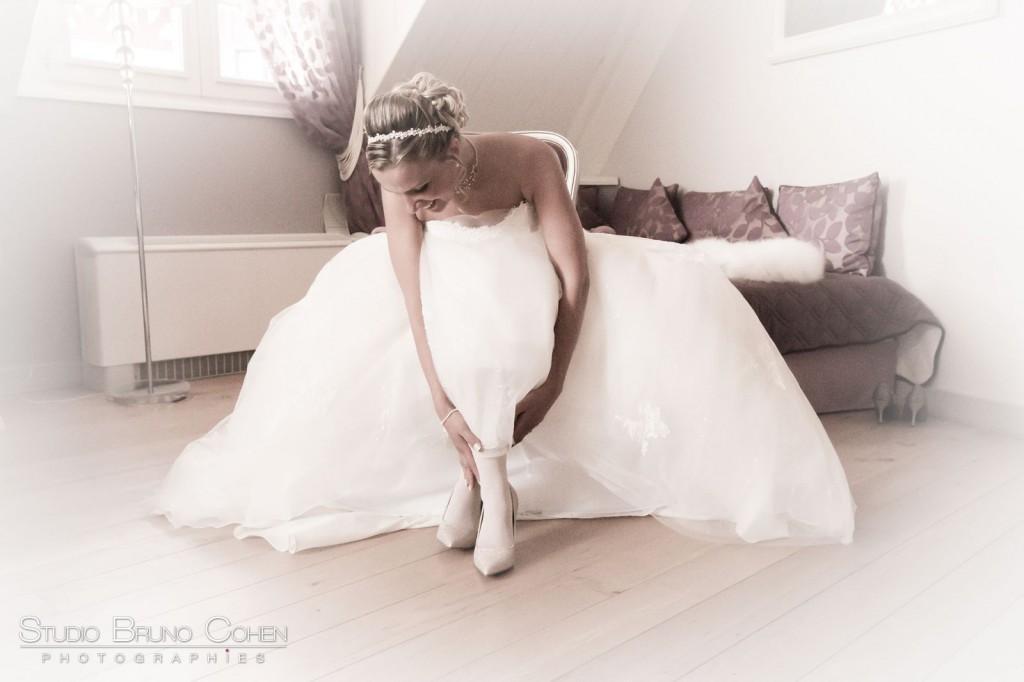 mariée assise enfile ses chaussures dans sa chambre au chateau de la tour gouvieux