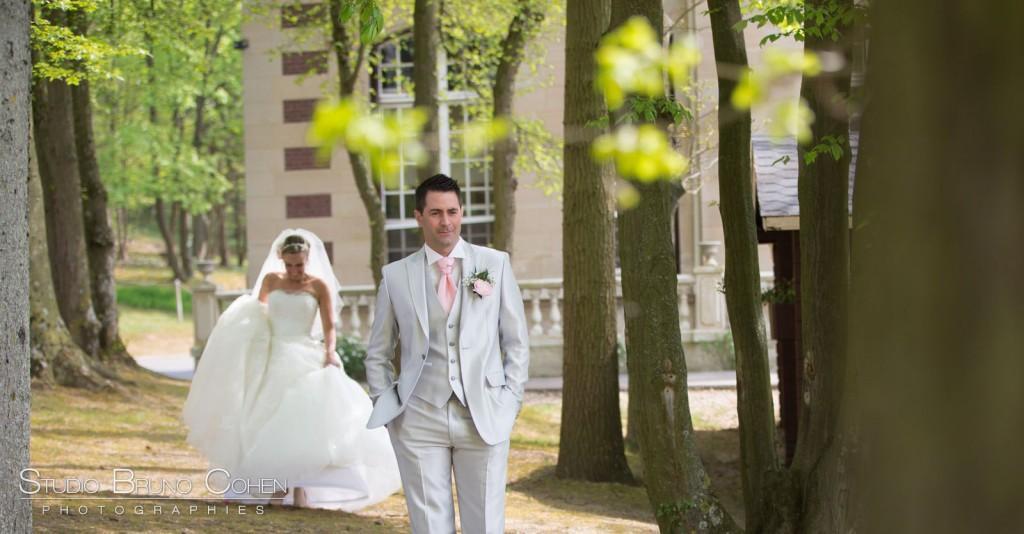 marié de face dans les jardins du chateau de la tour, la mariée marche vers lui dans son dos