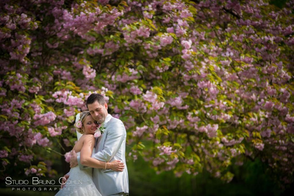 couple de mariés enlacés devant un cerisier en fleurs roses au parc du chateau de la Tour