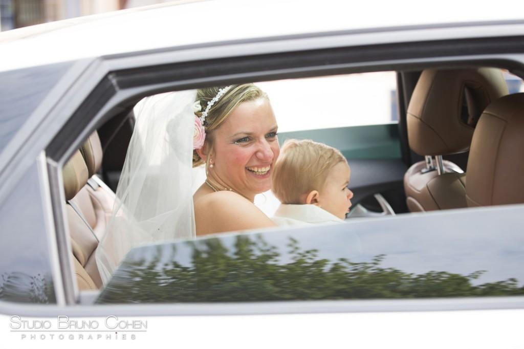 mariée souriante regardant par la fenetre d'une voiture