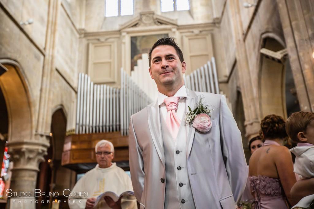 marié dans l'église de Gouvieux qui regarde la mariée entrer
