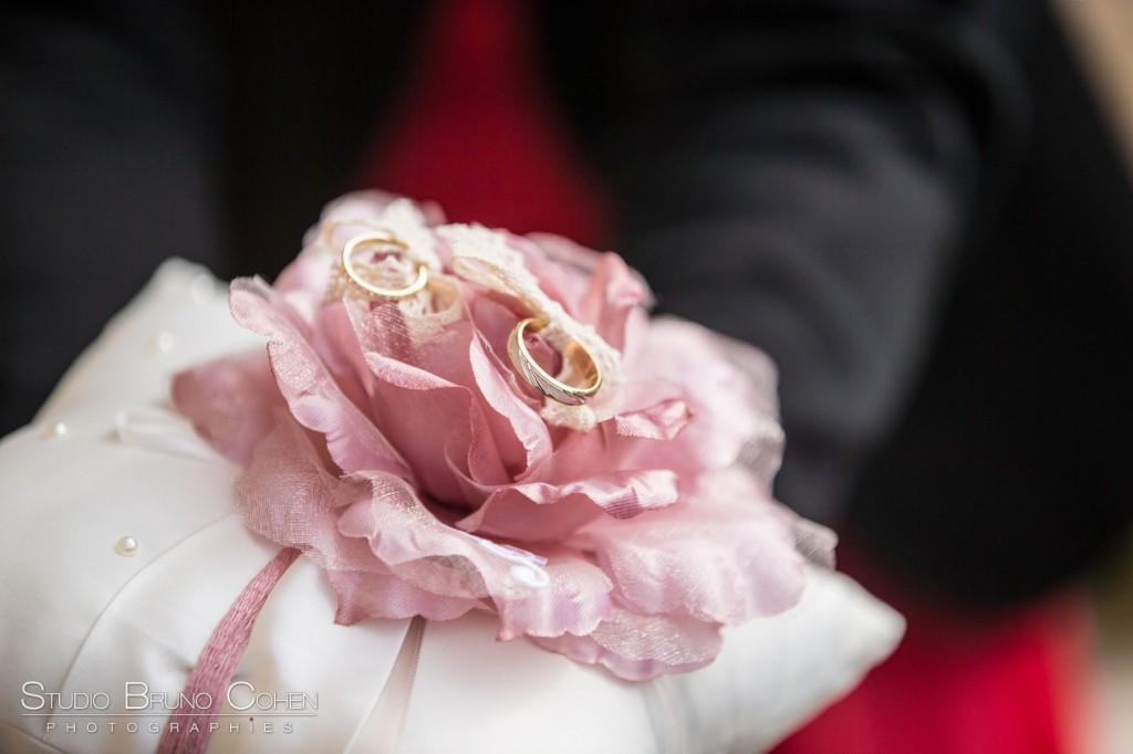 alliances sur un coussin blanc et rose