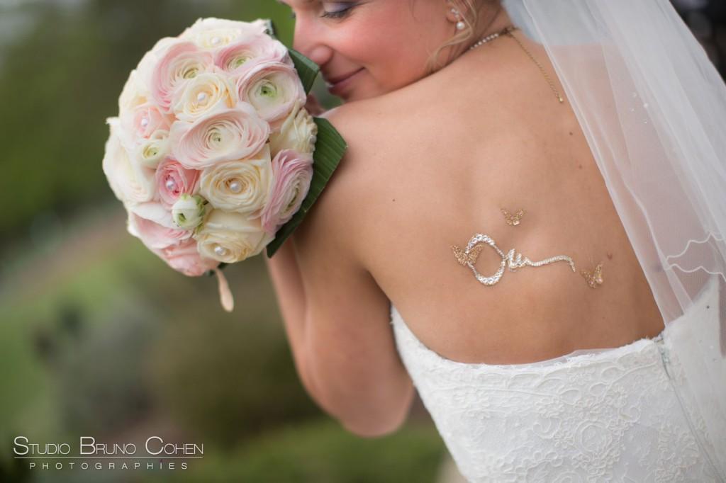 mariée de dos montrant son tatouage éphémère en strass et tenant son bouquet sur l'épaule