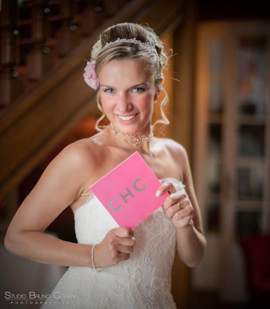 mariée blonde souriante tenant un livret rose Hotel Collection
