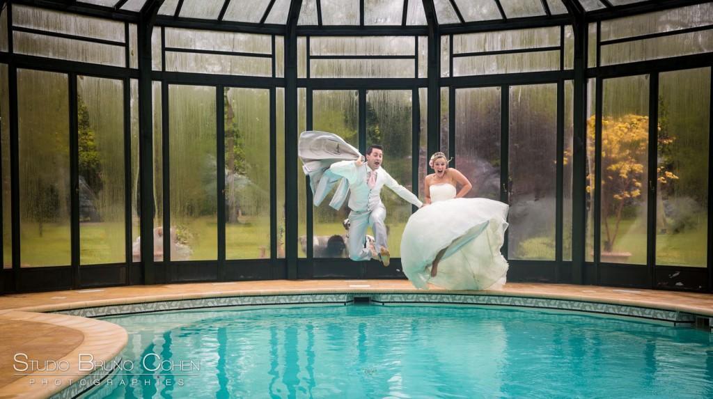 couple de mariés qui saute a pieds joints dans une piscine trash the dress