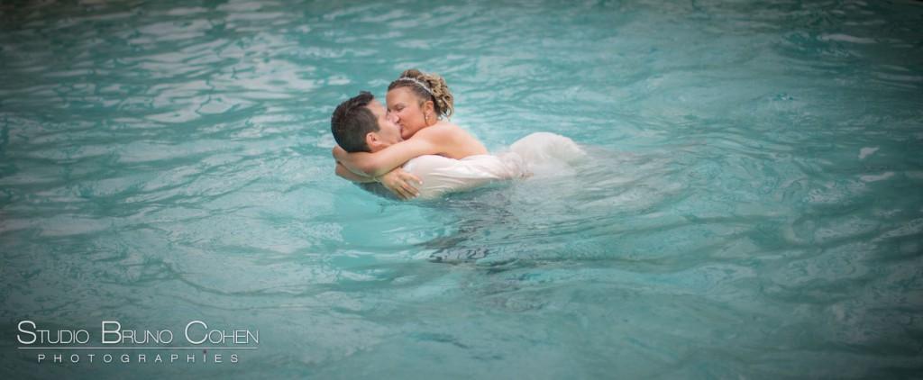 mariés qui s'embrassent dans un piscine à l'eau bleu turquoise