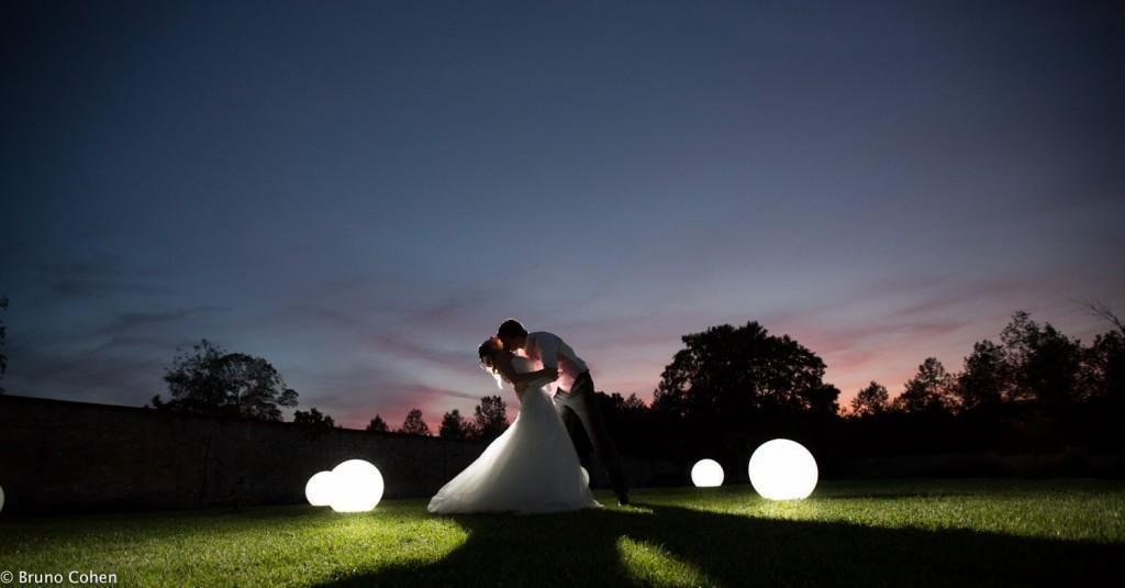 Dans le parc du Chateau de la Trie au crépuscule, un couple de mariés qui s'embrasse pendant le diner