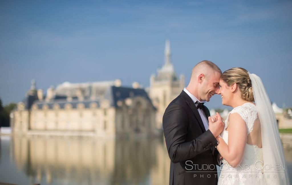 mariage a Chantilly, mariés de profils se regardent en souriant et se tenant les mains devant le chateau de Chantilly flou au fond, ciel bleu