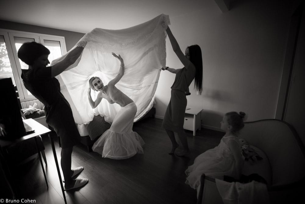 mariee avec ses deux temoins l'aide a mettre sa robe