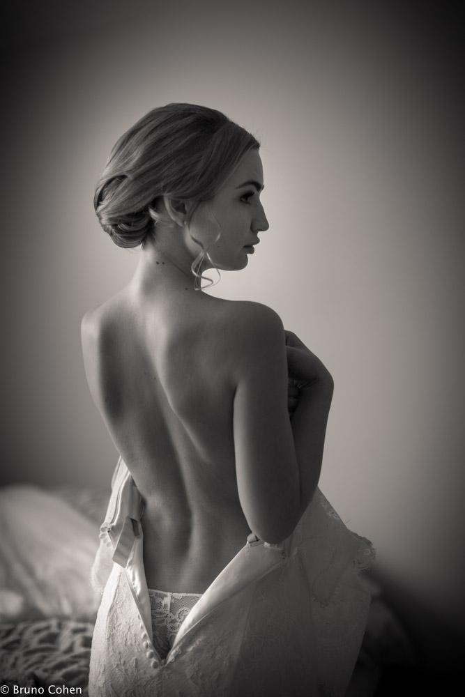 mariee le dos nus en train de mettre sa robe