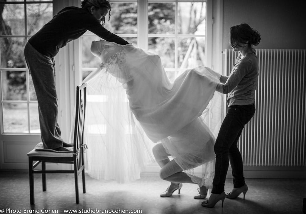 mariee enfile sa robe a l'aide de ses temoins