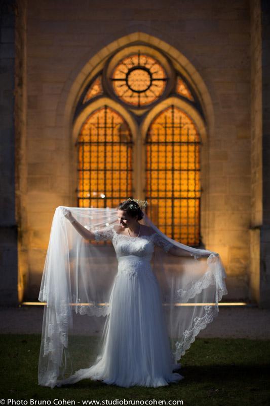 mariee joue avec son voile devant l'abbaye de royaumont