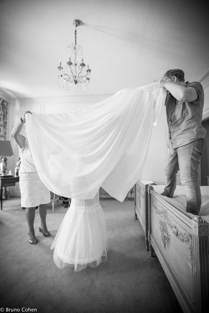 mariee avec invites qui l'aident a mettre sa robe