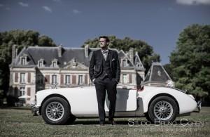 marié debout devant une voiture décapotable blanche au chateau de saint-remy-en-l'eau