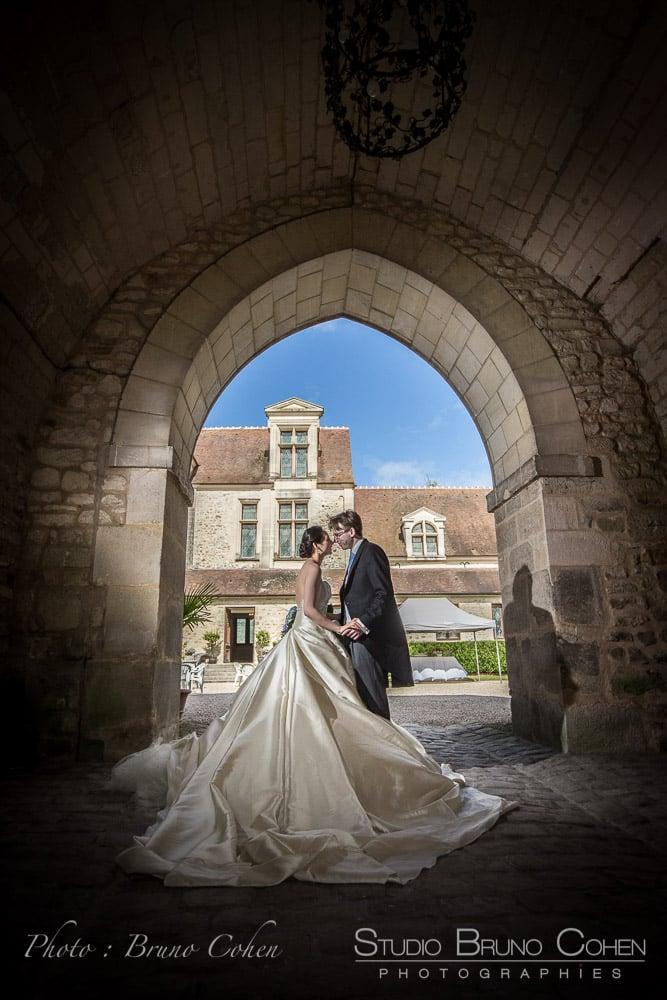 mariage couple de mariés qui s'embrassent sous le porche du Chateau de Pontarmé