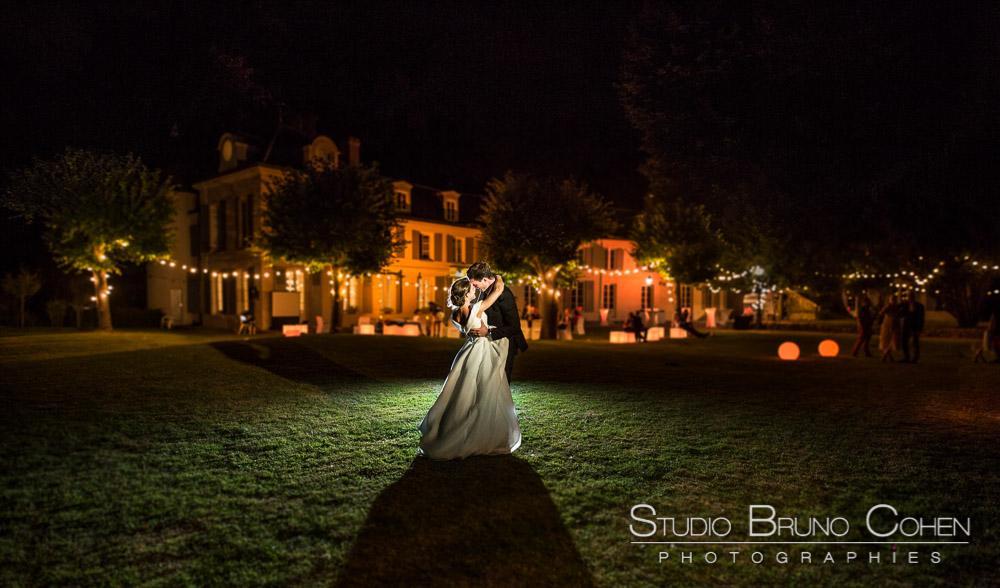 couple de mariés qui s'embrassent de nuit devant le chateau de Chaumontel