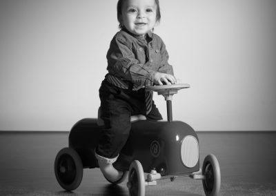 raphael-photo-portrait-enfant-voiture-jouet-studio-noir-et-blanc-sourire