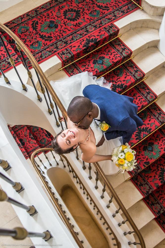 mariage a la mairie de Courbevoie, mariés qui s'embrassent dans un escalier rouge vus d'en haut