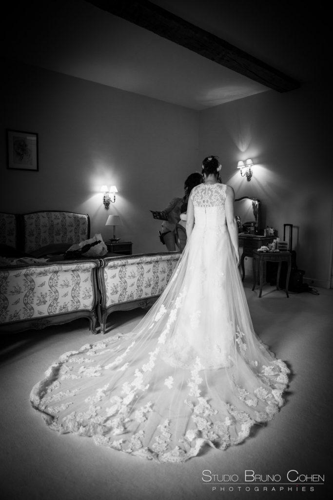mariee pose au milieu de la chambre pour montrer sa robe