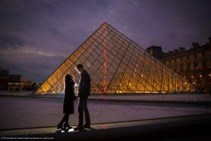 a couple in front of the Louvre Pyramid at twilight Paris