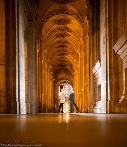 couple kissing in a corridor of the Louvre Museum Paris at night