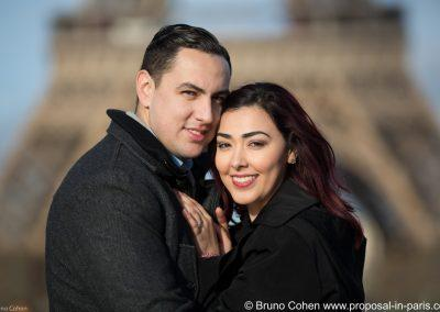 smiling couple facing the camera with blurried Eiffel Tower as a backdrop