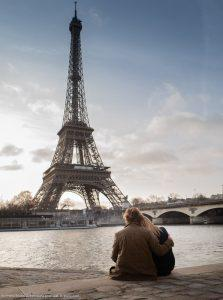 best spot in Paris couple in love seated along the Seine facing the Eiffel Tower at sunrise