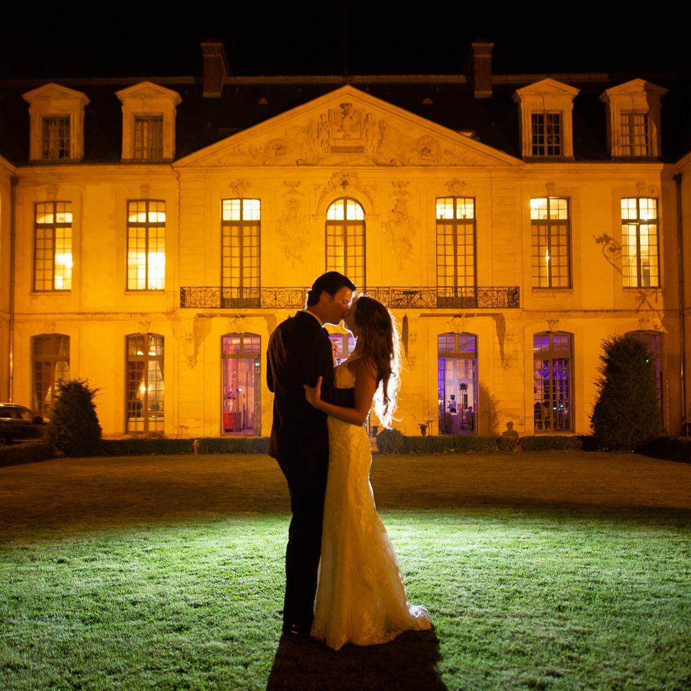 deux mariés s'embrassent de nuit dans la cour du Chateau d'Ermenonvilleparis-senlis