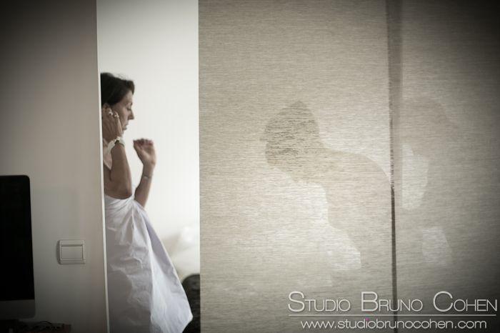 silhouette d'une mariée qui s'habille derrière un paravent en toile beige