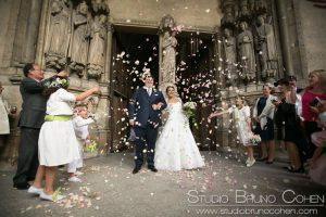 couple de mariés sous les confettis à la sortie d'une messe de mariage à l'église Saint Germain L'Auxerrois Paris