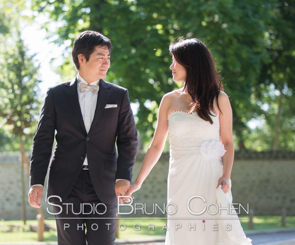mariage couple de mariés se tenant par la main en marchant en se regardant sur un fond de foret