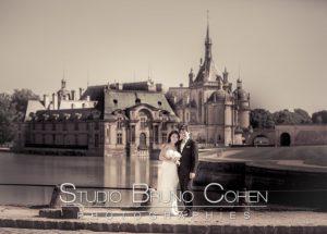 couple de mariés posant devant le chateau de Chantilly, couleurs sépia