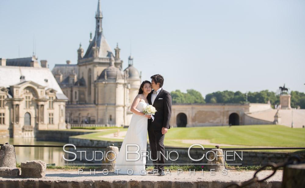 mariage au chateau de Chantilly, couple asiatique ou l'homme embrasse la jeune femme sur la joue