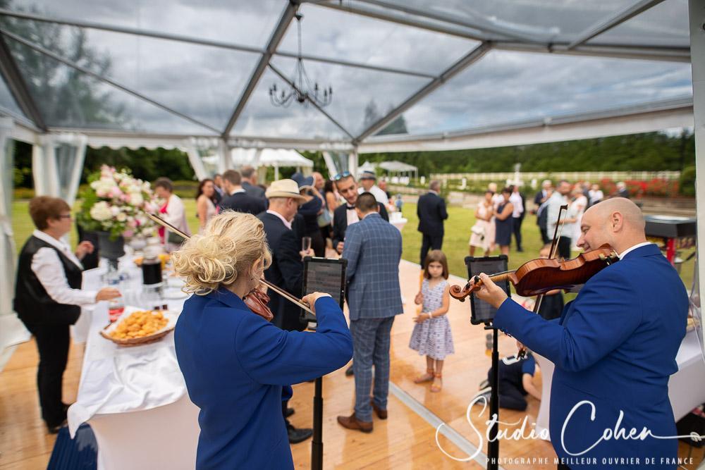 cocktail de mariage sous une veranda avec deux violonistes au premier plan, Isabelle et Lionel Turchi