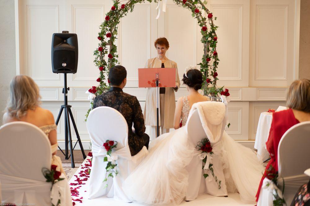 cérémonie laique de mariage à l'hotel Tiara Montroyal Chantilly dans le salon Debussy, deux mariés de dos, arche fleurie et officiante de face leur parlant